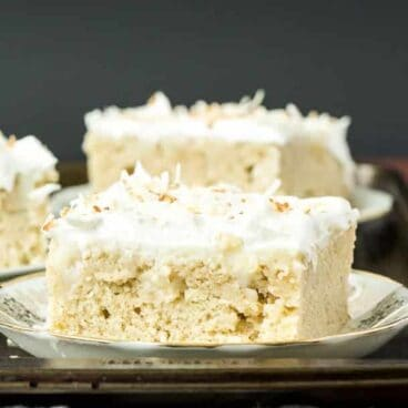 Coconut Cream Poke Cake: Homemade vanilla cake filled with homemade coconut cream pudding, topped with whipped cream and toasted coconut -- the cake for coconut lovers! Make it from scratch or use cake mix or pudding mix to make it quick and easy! www.thereciperebel.com