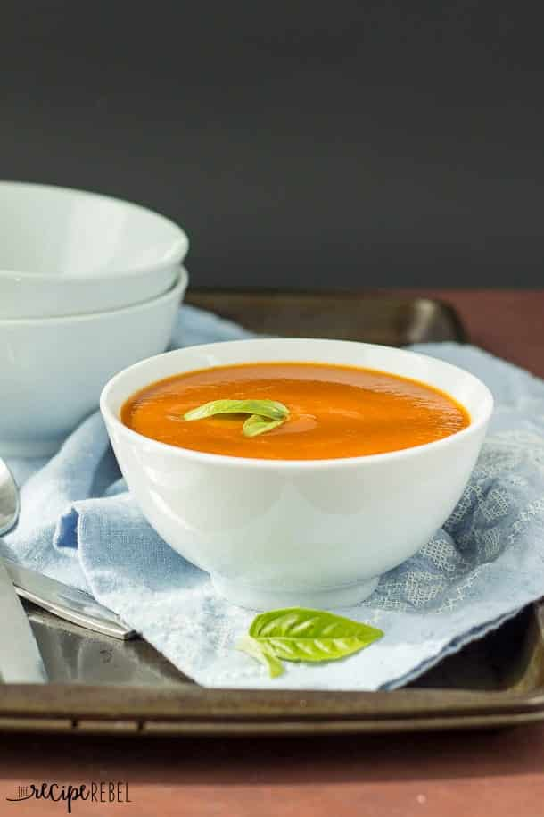 white bowl of slow cooker creamy tomato vegetable soup on blue towel