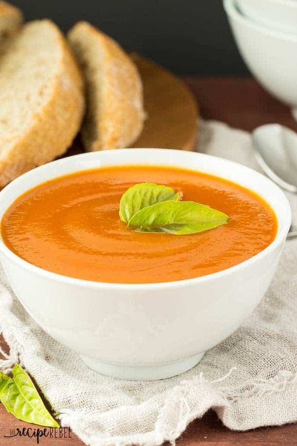 close up image of tomato vegetable soup in white bowl with bread behind