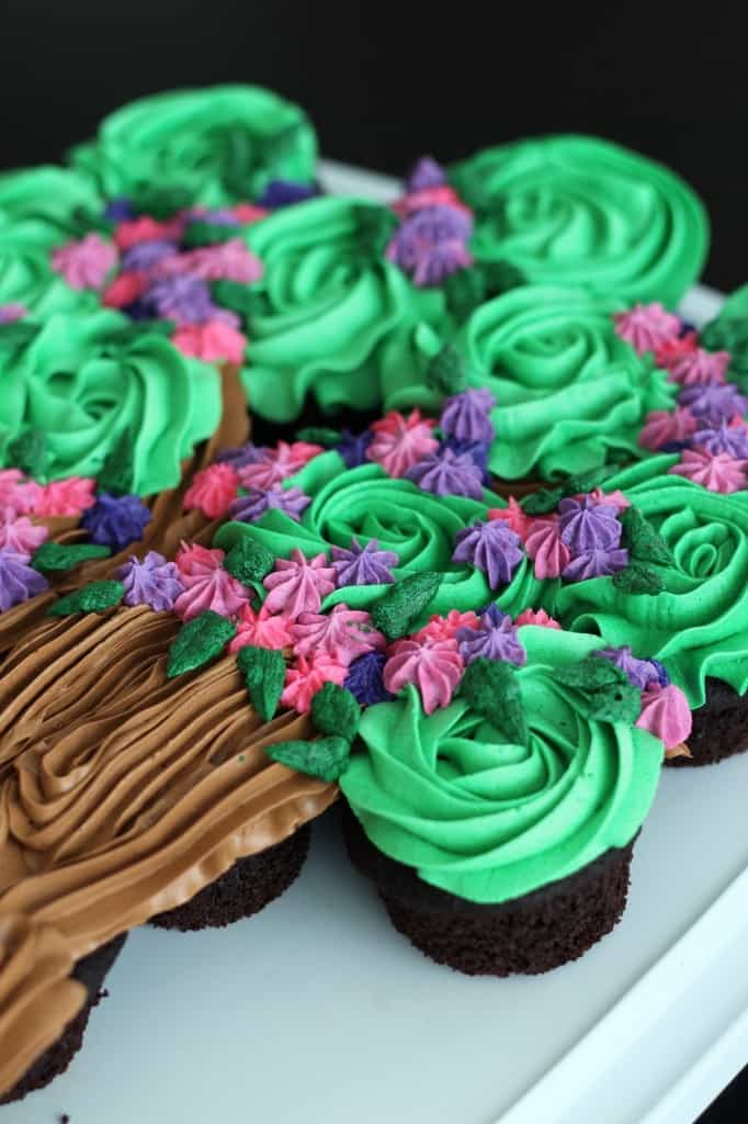 close up image of cupcake cake with flowers and leaves