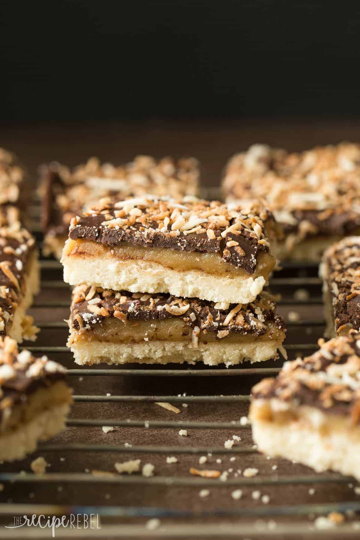 stack of two samoa shortbread bars on cooling rack with bars all around