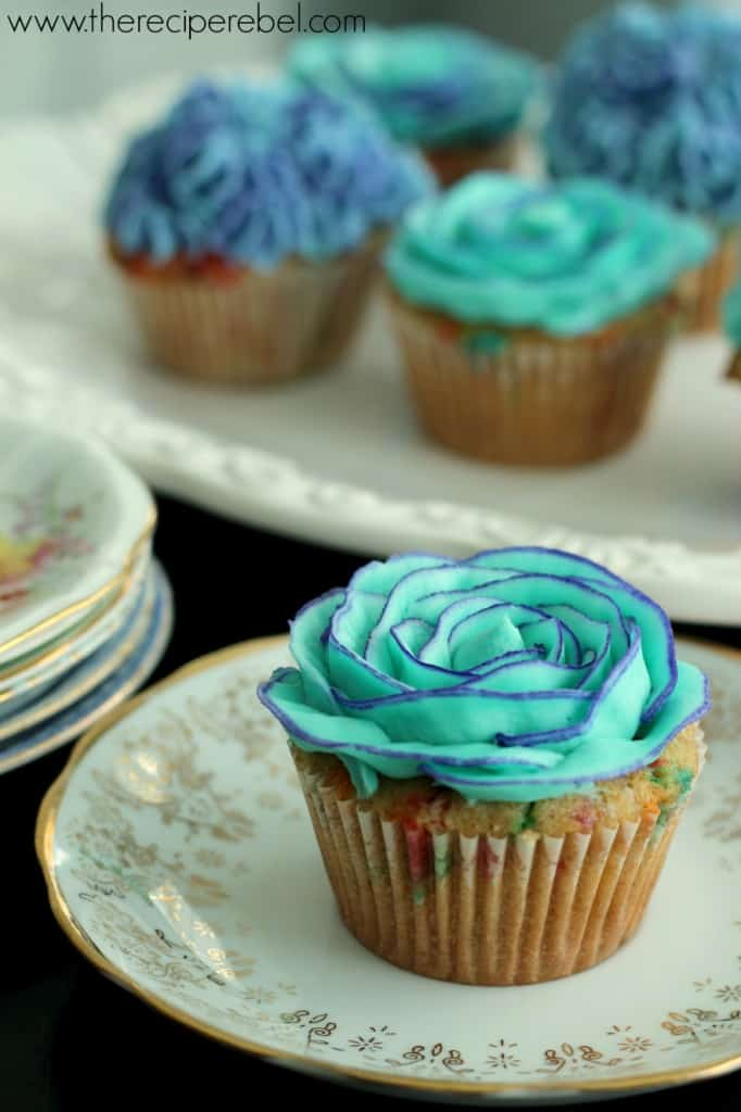 whole wheat funfetti cupcakes with blue frosting roses on white and gold china plate