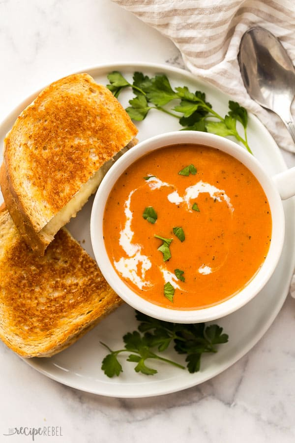 creamy tomato soup and grilled cheese on white plate