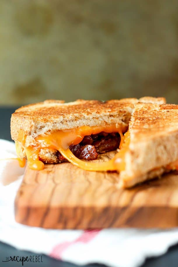 bacon jam grilled cheese cut open on wooden cutting board