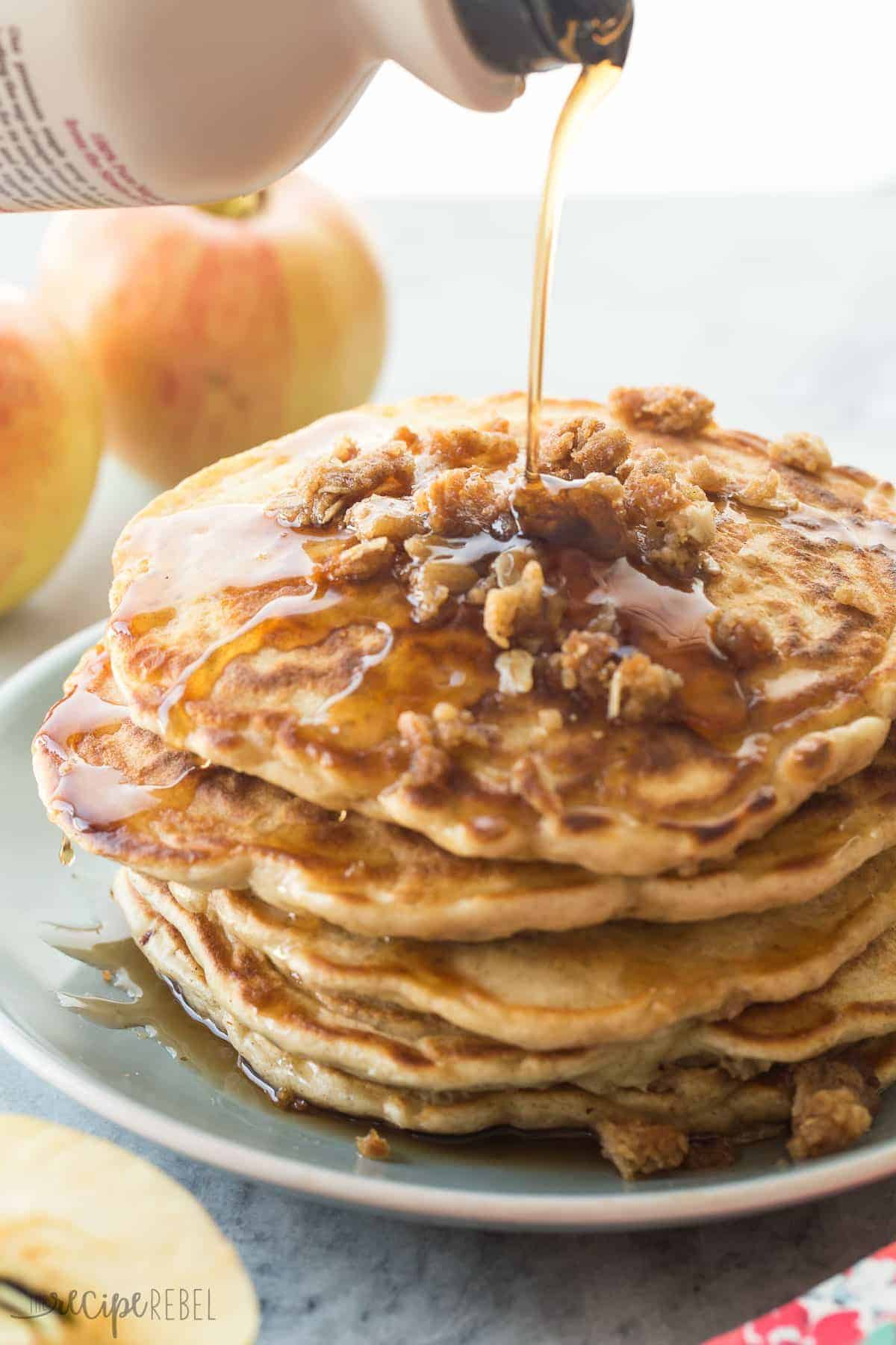 stack of pancakes with streusel crumbles on down and drizzle of syrup