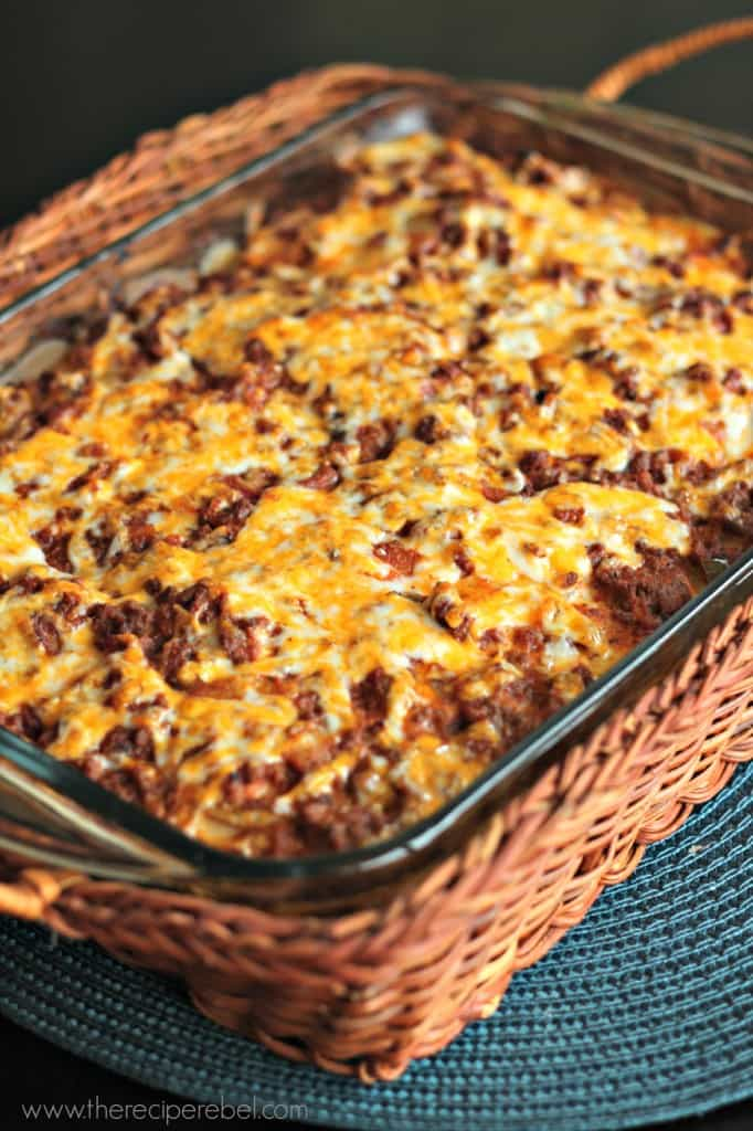 close up image of mexican scalloped potatoes in glass baking dish in basket