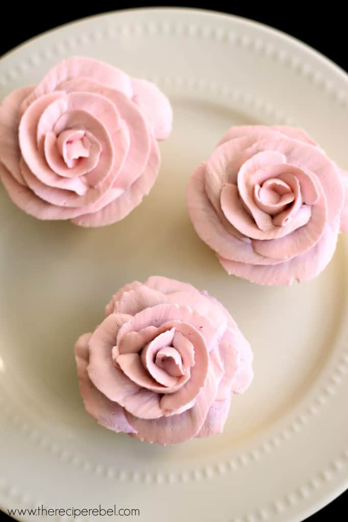 overhead image of lemon white chocolate cupcakes on white plate with pink frosting roses