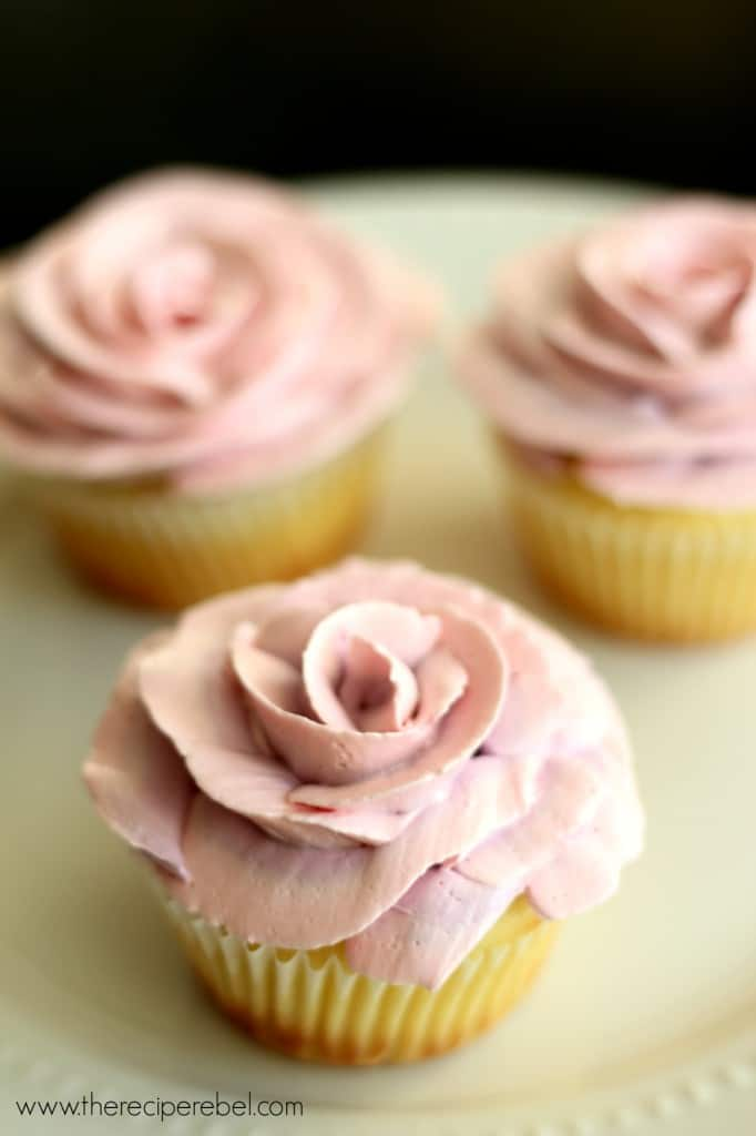 close up image of lemon cupcakes with white chocolate frosting piped in a rose