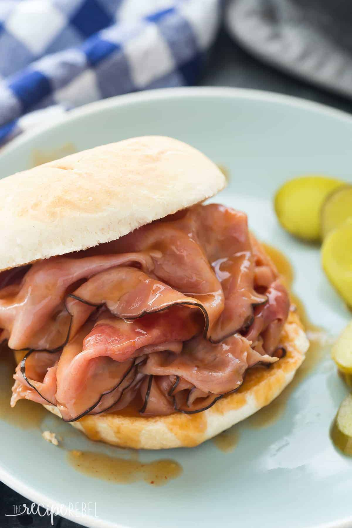 ham in barbecue sauce on white bun on blue plate with pickles on the side