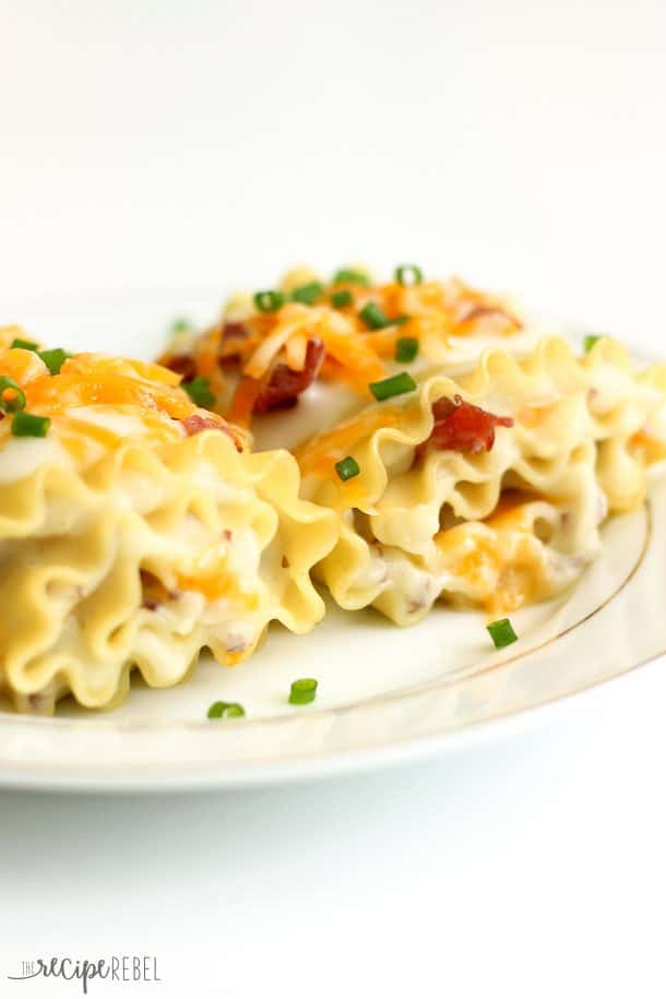 lasagna noodles rolled up with mashed potatoes and cheese and topped with bacon and chives