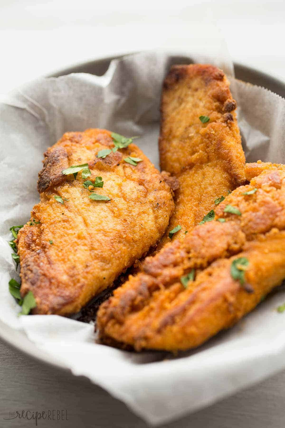 three pieces of oven fried chicken on a grey plate lined with parchment paper sprinkled with parsley