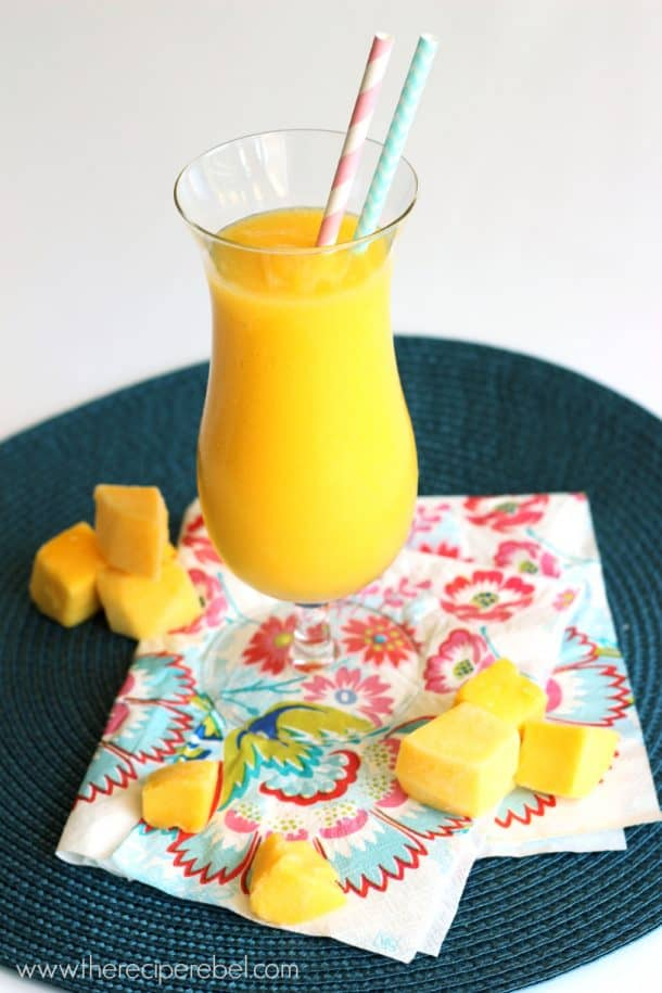 mango slush in tall glass with frozen mango chunks all around