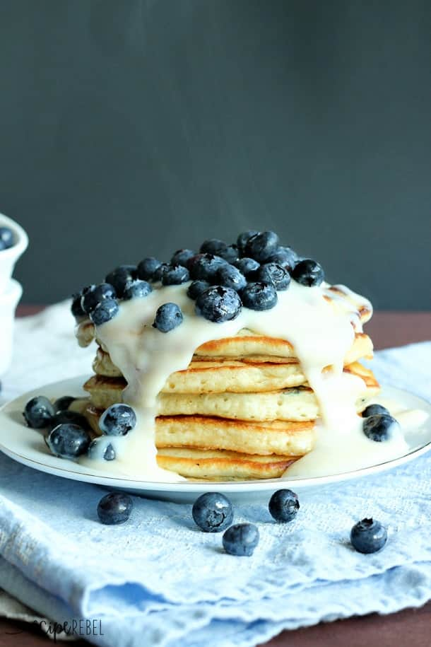 Blueberries 'n' Cream Pancakes: Super easy, fluffy pancakes topped with vanilla custard sauce and fresh blueberries! The perfect breakfast to use up those summer berries. www.thereciperebel.com