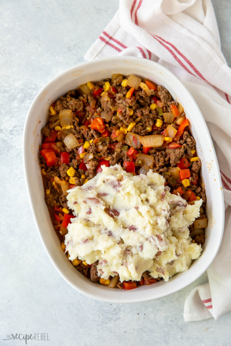mashed potatoes being spread over shepherds pie filling