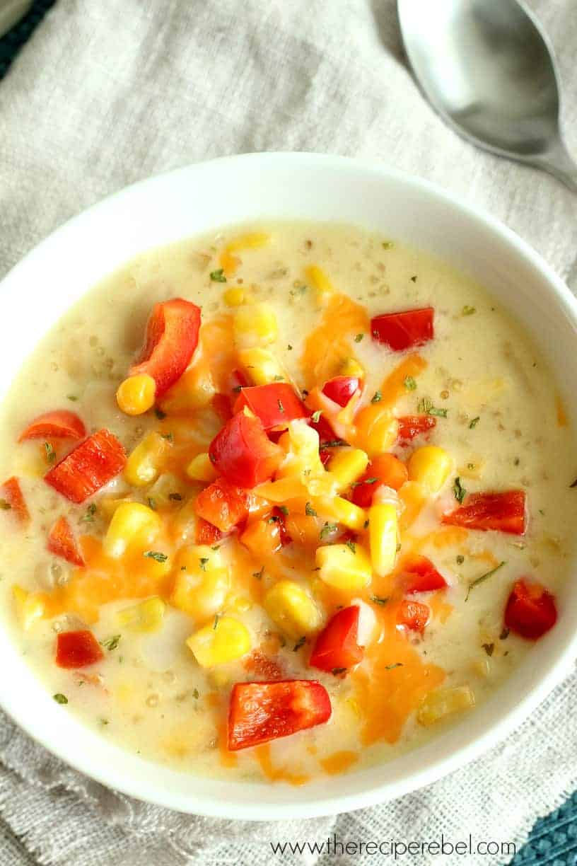 quinoa corn chowder in white bowl topped with red peppers and corn