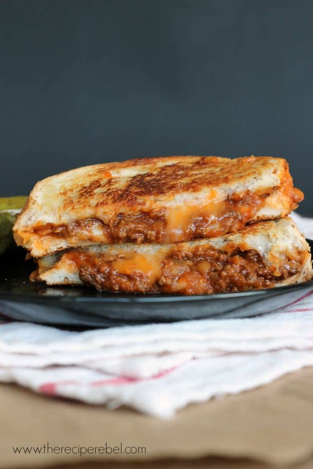 sloppy joe grilled cheese cut in half stacked on a black plate