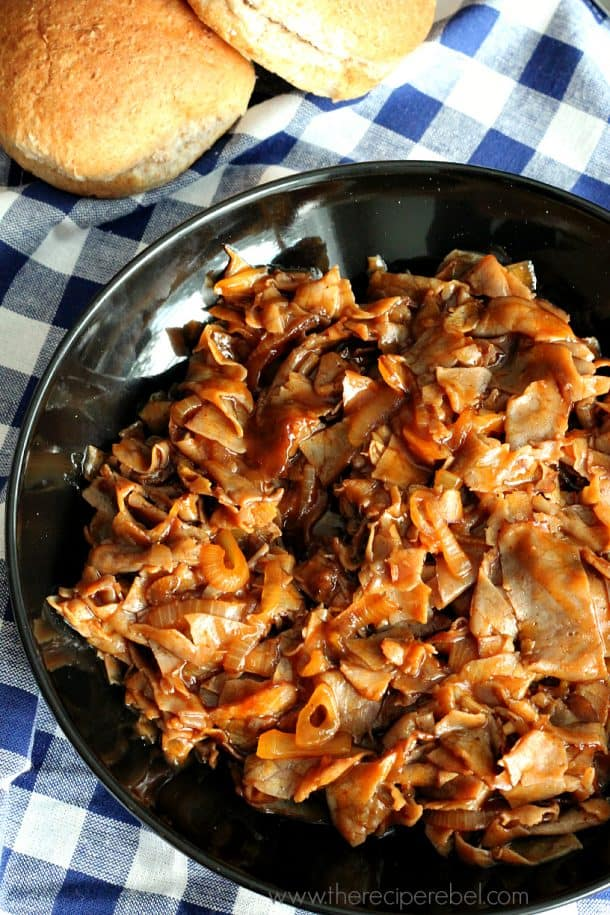thinly sliced beef with onions in barbecue sauce on large black plate