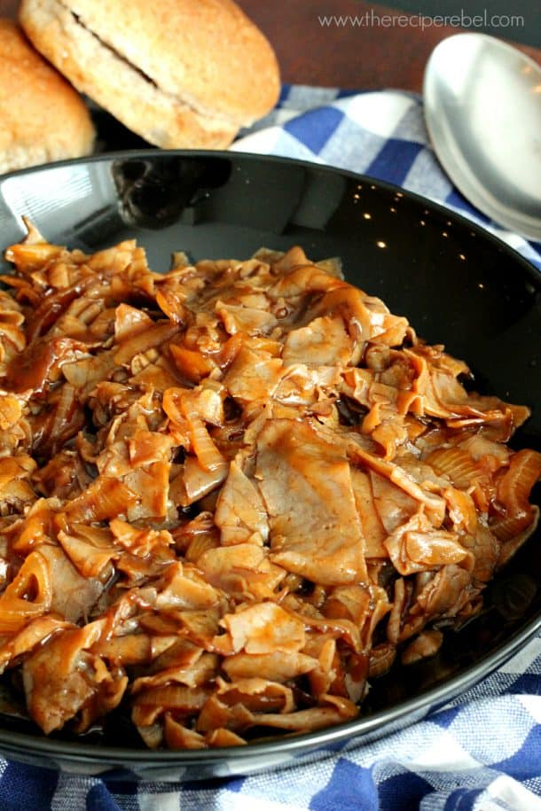 close up of shredded barbecue beef in large black serving bowl