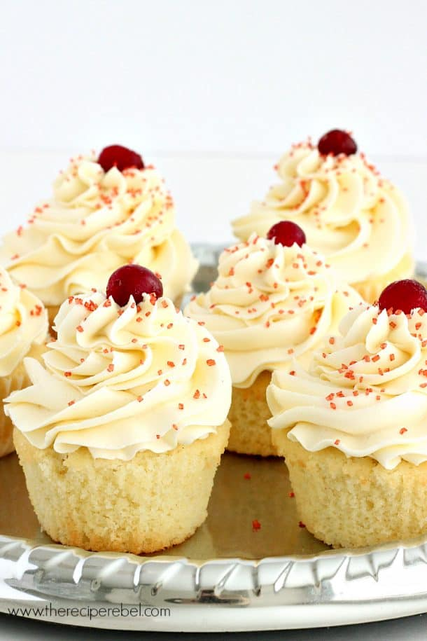 Perfectly sweet and fluffy vanilla cupcakes filled with sweet, tart cranberry filling and topped with a silky white chocolate buttercream -- perfect for the holidays! www.thereciperebel.com