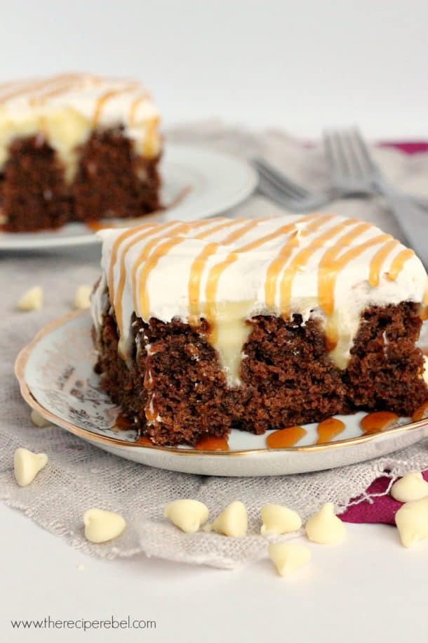 piece of gingerbread poke cake on plate with whipped cream and caramel sauce