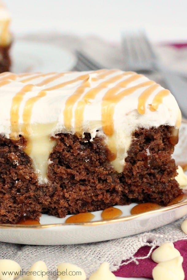 close up of white chocolate gingerbread poke cake with whipped cream and caramel sauce