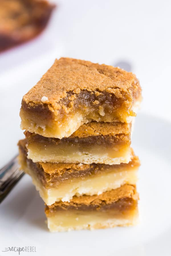 butter tart squares with bite stack of four on white background