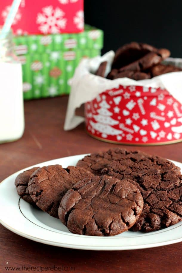 gluten free dairy free chocolate cookies on white plate in front of christmas tins
