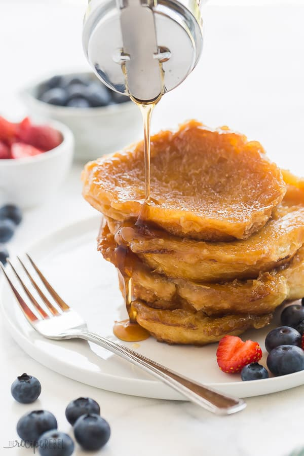 caramel french toast stack on white plate with syrup drizzled over top