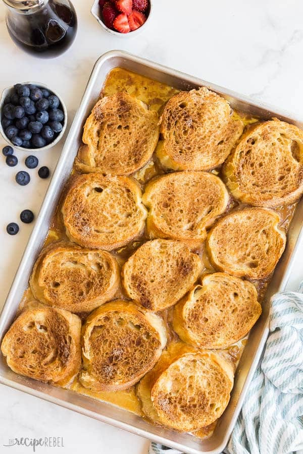 overnight caramel french toast on sheet pan with fresh blueberries on the side