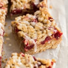 close up image of one cranberry bar with drizzle of glaze