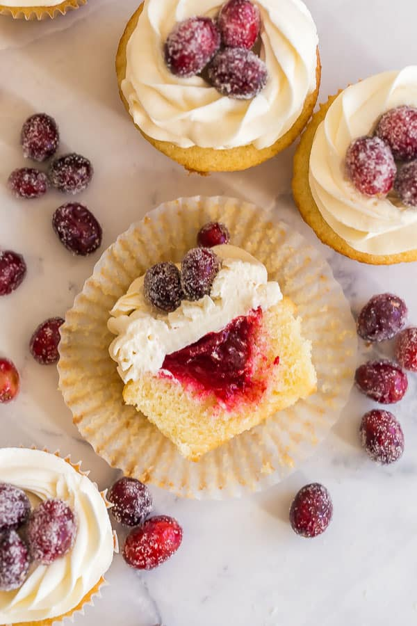 cranberry vanilla cupcakes cut in half and lying on paper liner