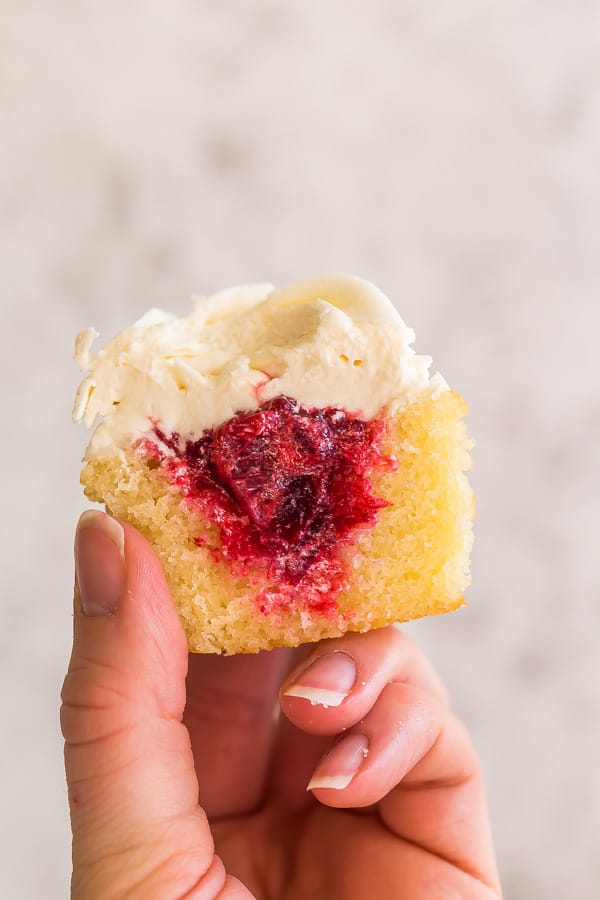 hand holding up cranberry cupcake revealing filling