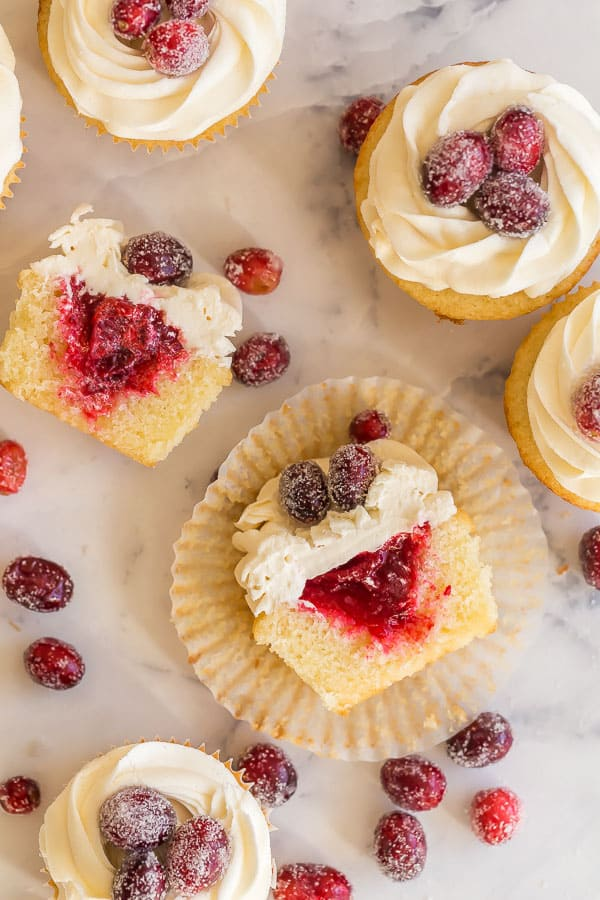 overhead image of cranberry vanilla cupcakes with one cut open
