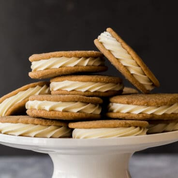 white chocolate gingersnap oreos piled on a white cake plate