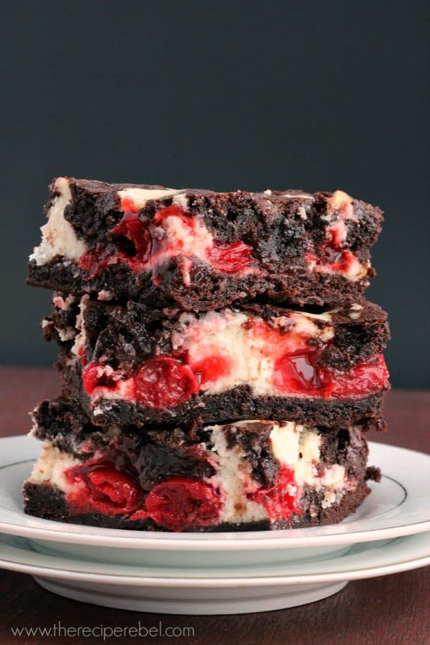 stack of 3 cherry cheesecake brownies on white plate against a black background