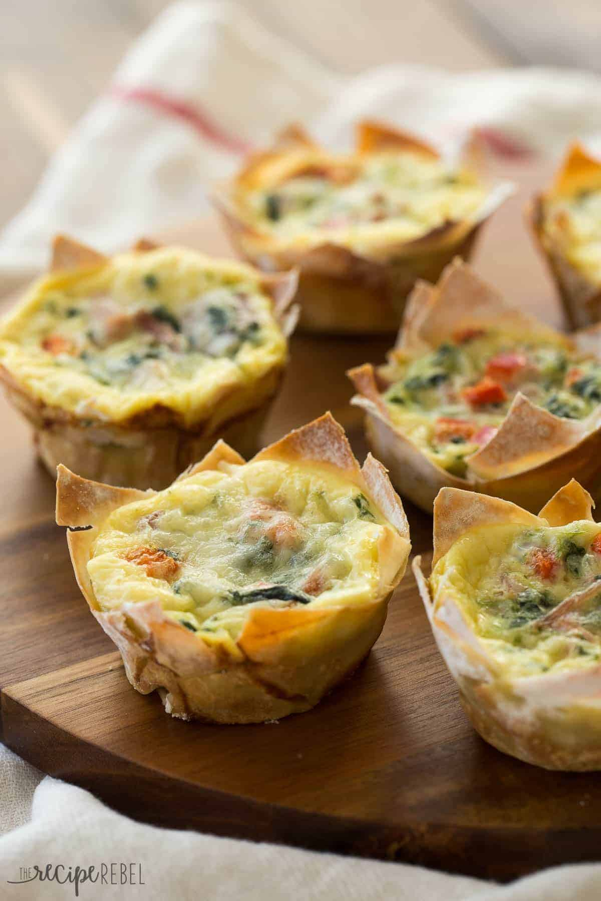 mini wonton quiche with spinach and peppers on a wooden board