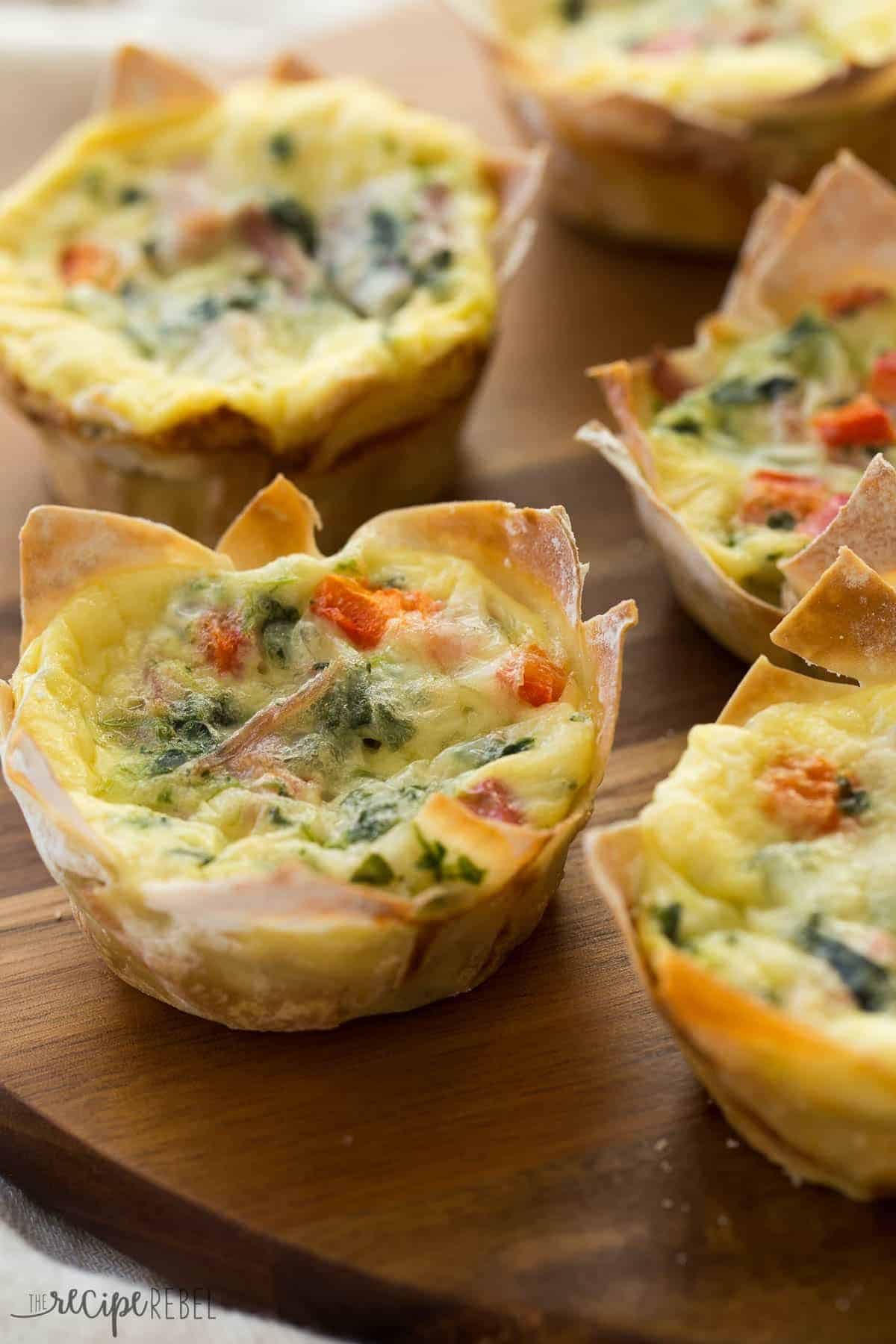 mini quiche in wonton wrappers on a wooden board