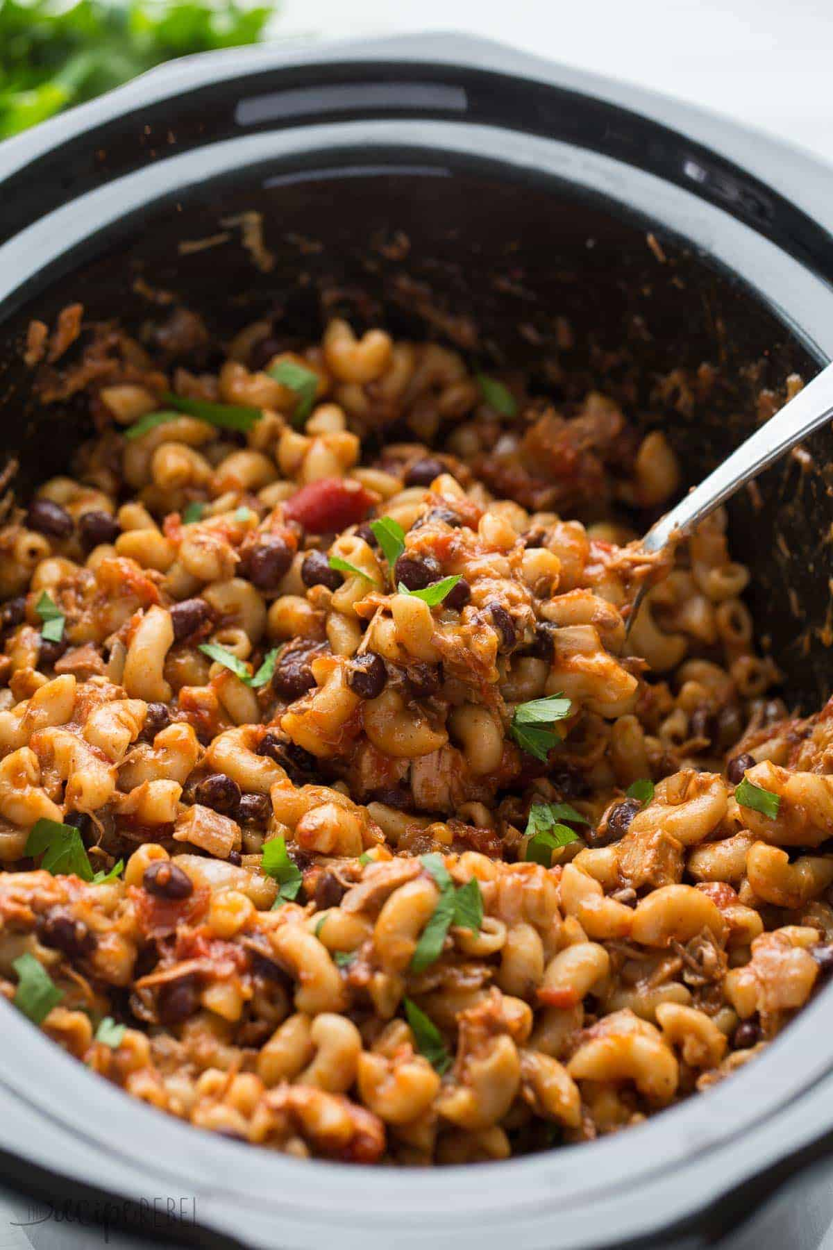metal spoon scooping bbq chicken chili mac from black slow cooker