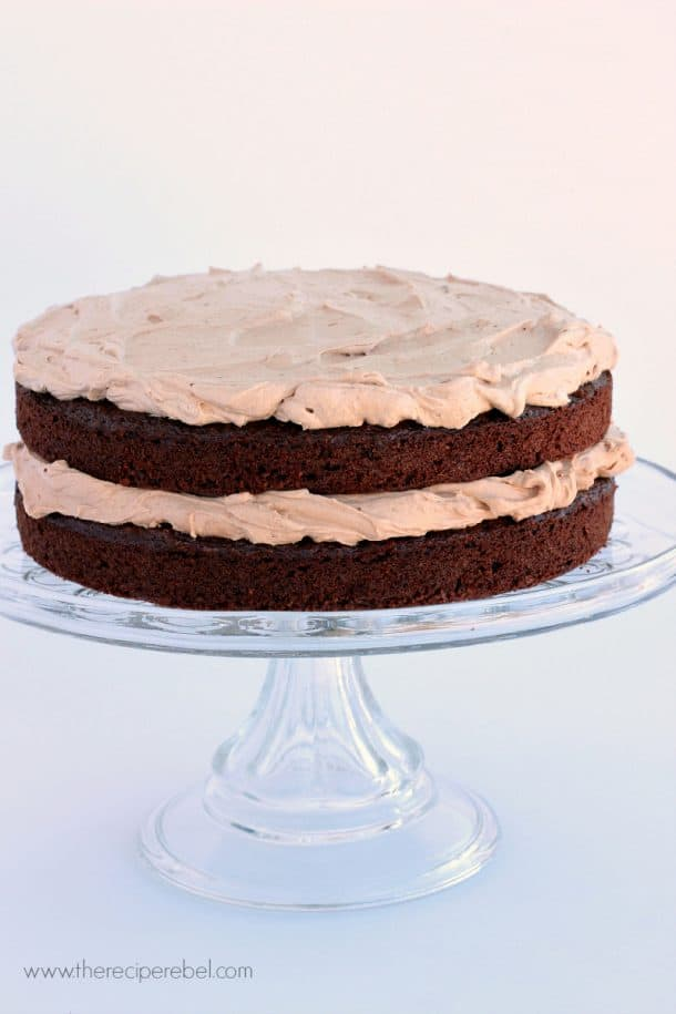 two layer mexican chocolate cake with milk chocolate frosting on clear glass cake plate