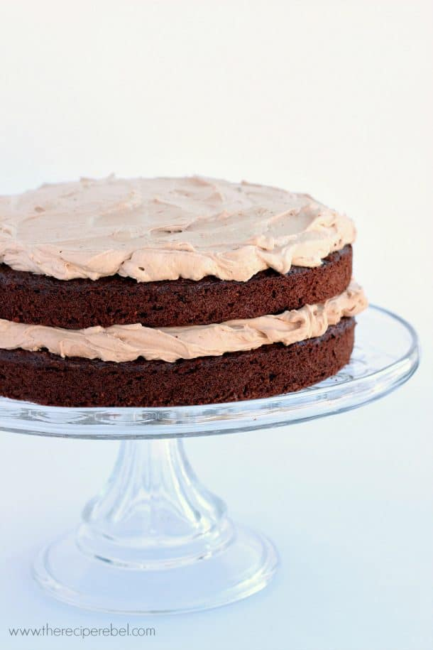 two layer gluten free chocolate cake on clear cake plate on white background