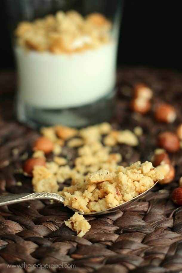 spoonful of hazelnut and brown sugar crumble resting on brown placemat