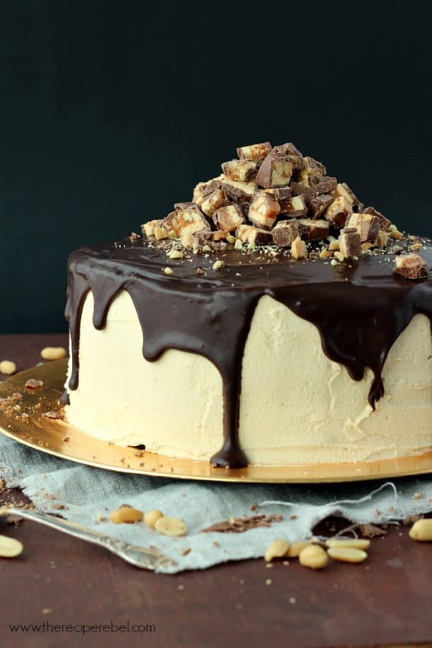 Snickers Cheesecake Cake and a Blog Birthday: two layers of rich, fudgy cake and 2 layers of creamy chocolate peanut butter cheesecake, with peanut butter frosting, caramel, salted peanuts and chopped Snickers bars. Plus a giveaway! www.thereciperebel.com
