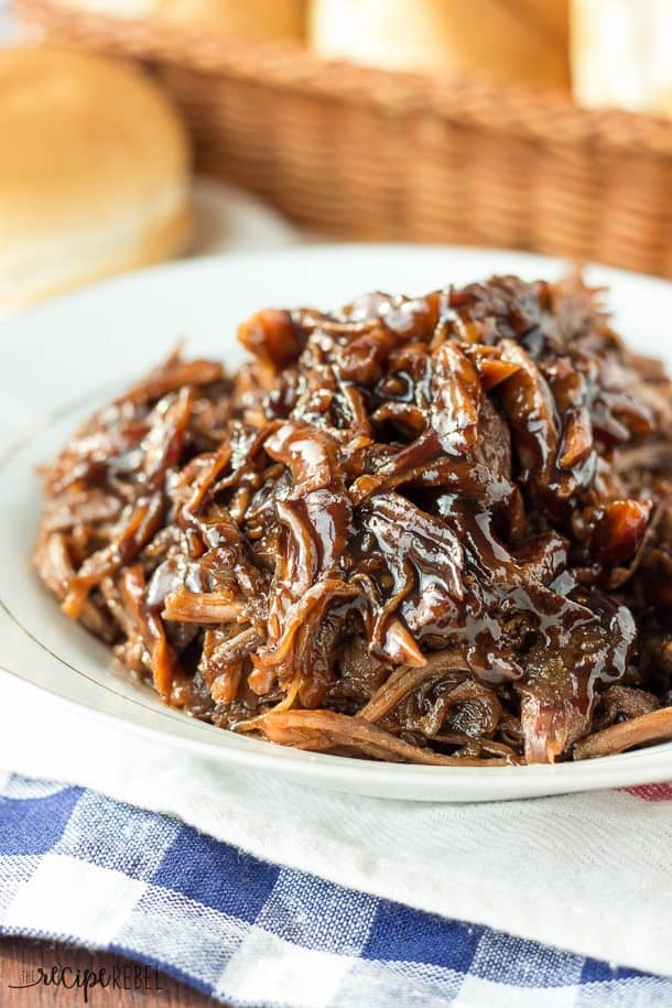slow cooker honey balsamic pulled pork piled on white plate with buns in background