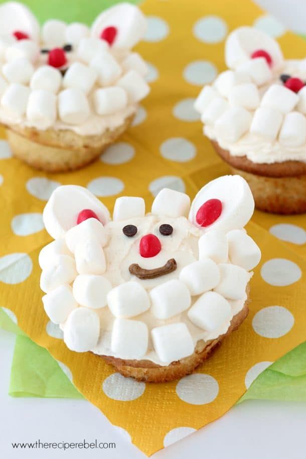 cupcakes decorated with white frosting mini marshmallows and jelly beans to look like a lamb