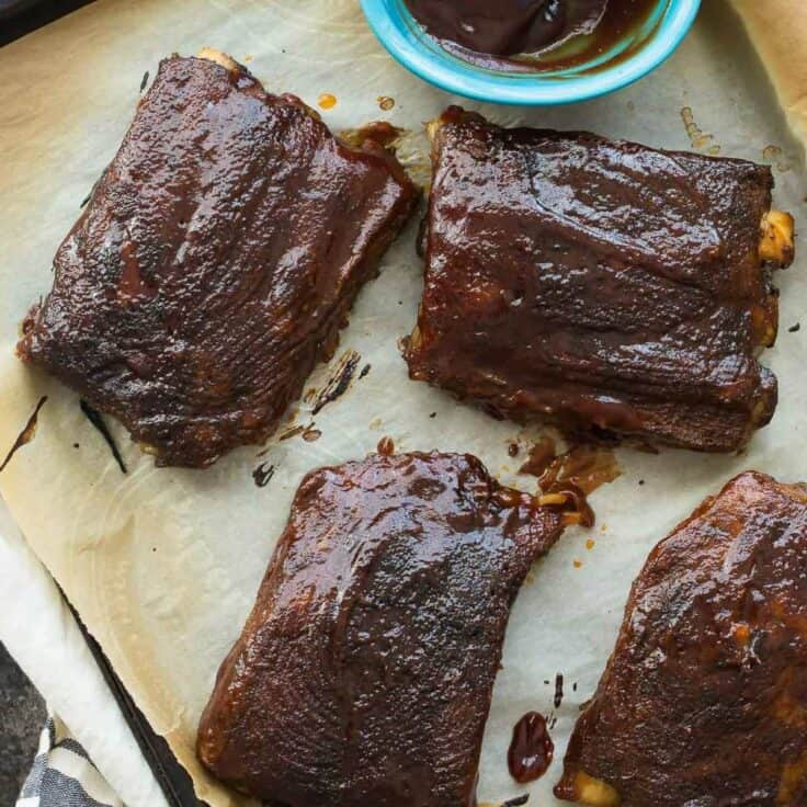 slow cooker bbq ribs on sheet pan with parchment paper and extra bbq sauce