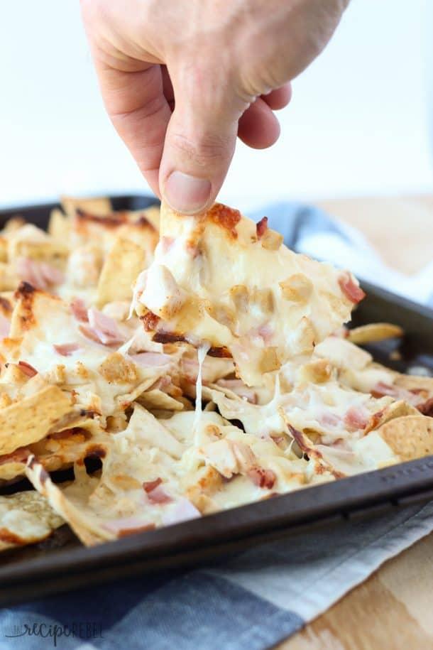 chicken cordon bleu nachos on sheet pan with hand pulling one chip