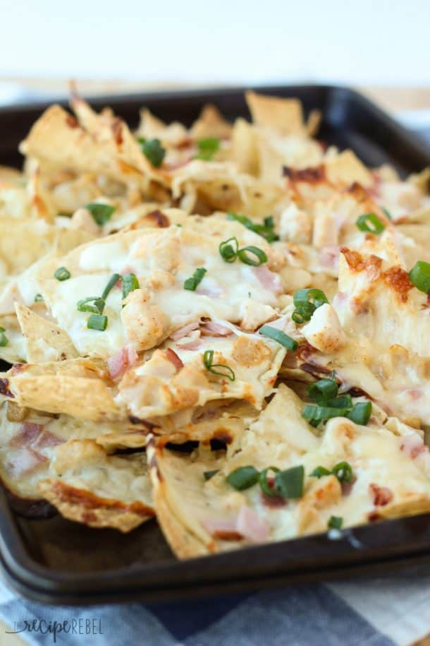 chicken cordon bleu nachos on dark sheet pan topped with green onions