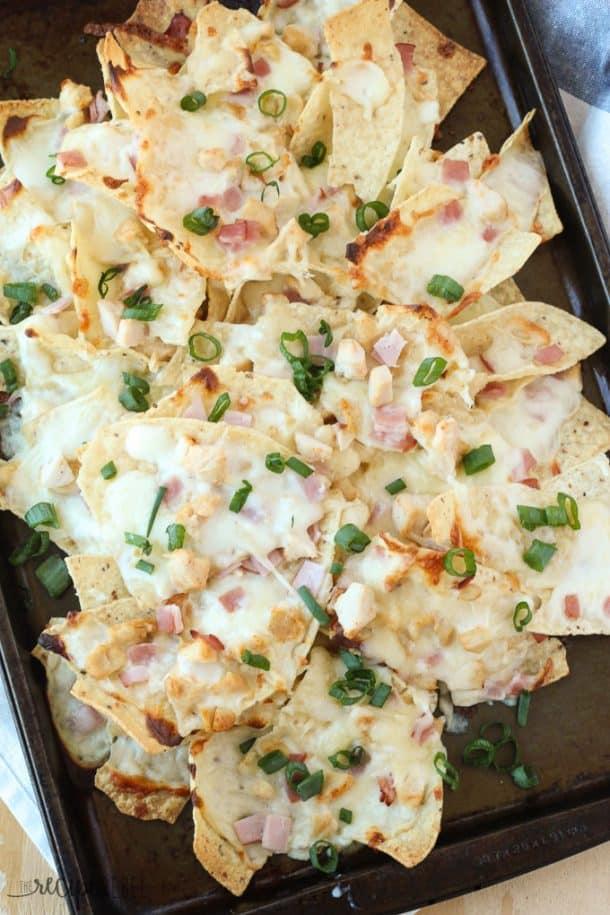 chicken cordon bleu nachos overhead on dark sheet pan