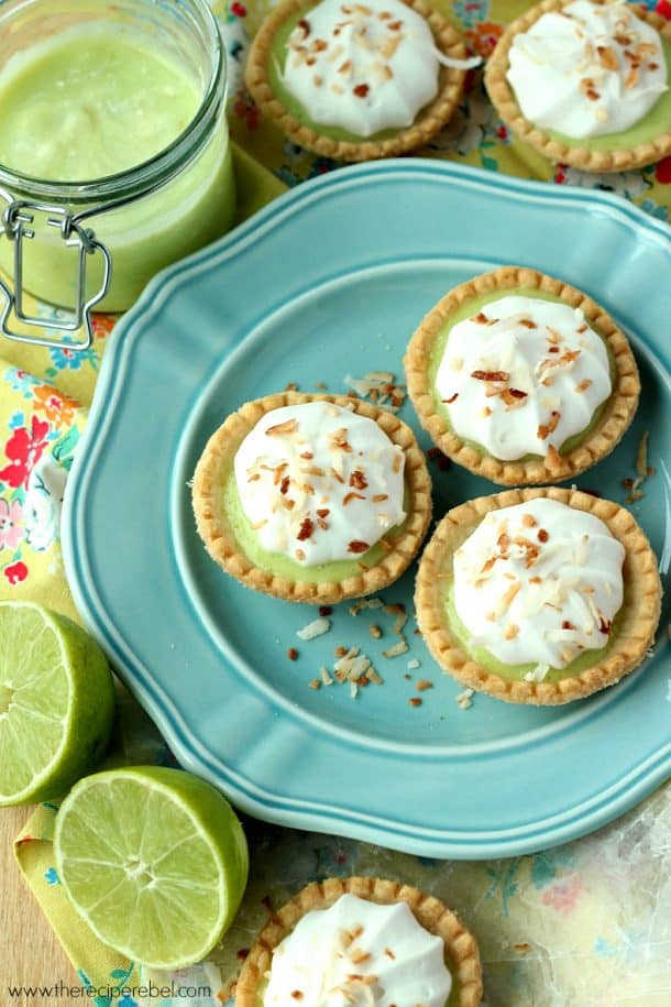 overhead image of blue plate with three coconut lime tarts and lime halves on the side