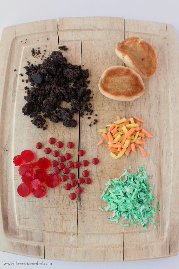 ingredients to make sugar cookie tacos including candies shredded coconut oreo crumbles and sugar cookie shells